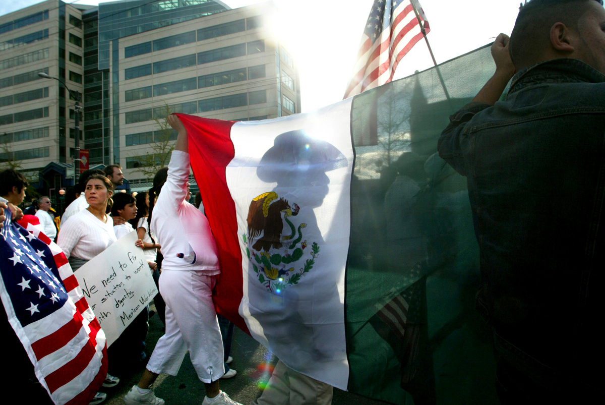 A man who didn't want to give his name, marches in front of a Mexican flag with 15,000 others in Seattle during a rally for immigration rights on April 10, 2006.  Asking for amnesty, equal rights, open borders, recognition and respect they demonstrated in solidarity with hundreds of thousands across America demanding immigration reform.