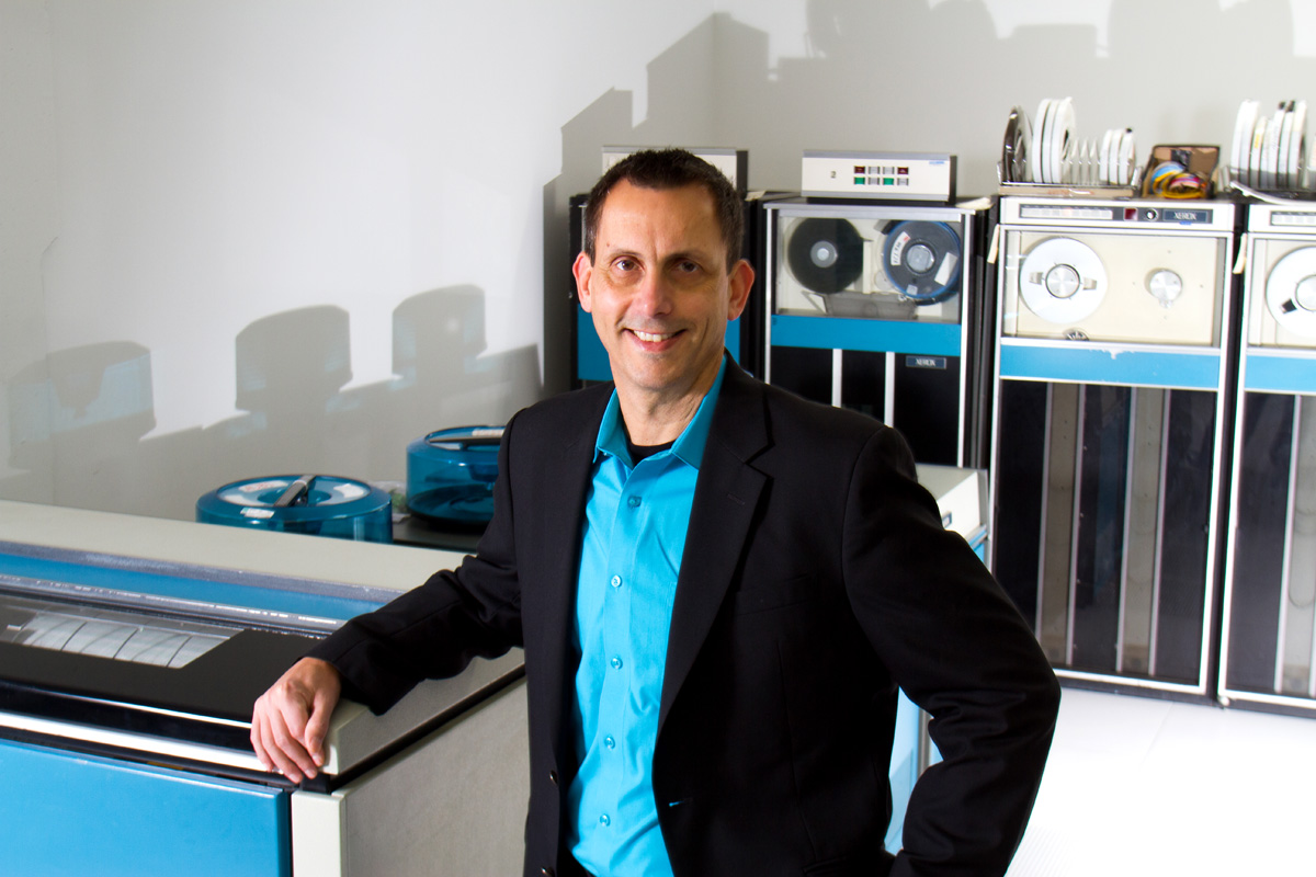 Senior Vice President and Chief Information Officer of Seattle Children's Hospital, Wes Wright, is photographed next to a Sigma 9 Mainframe printer at the Living Computer Museum in Seattle, Washington.  The Sigma 9 tape drives are in the background.