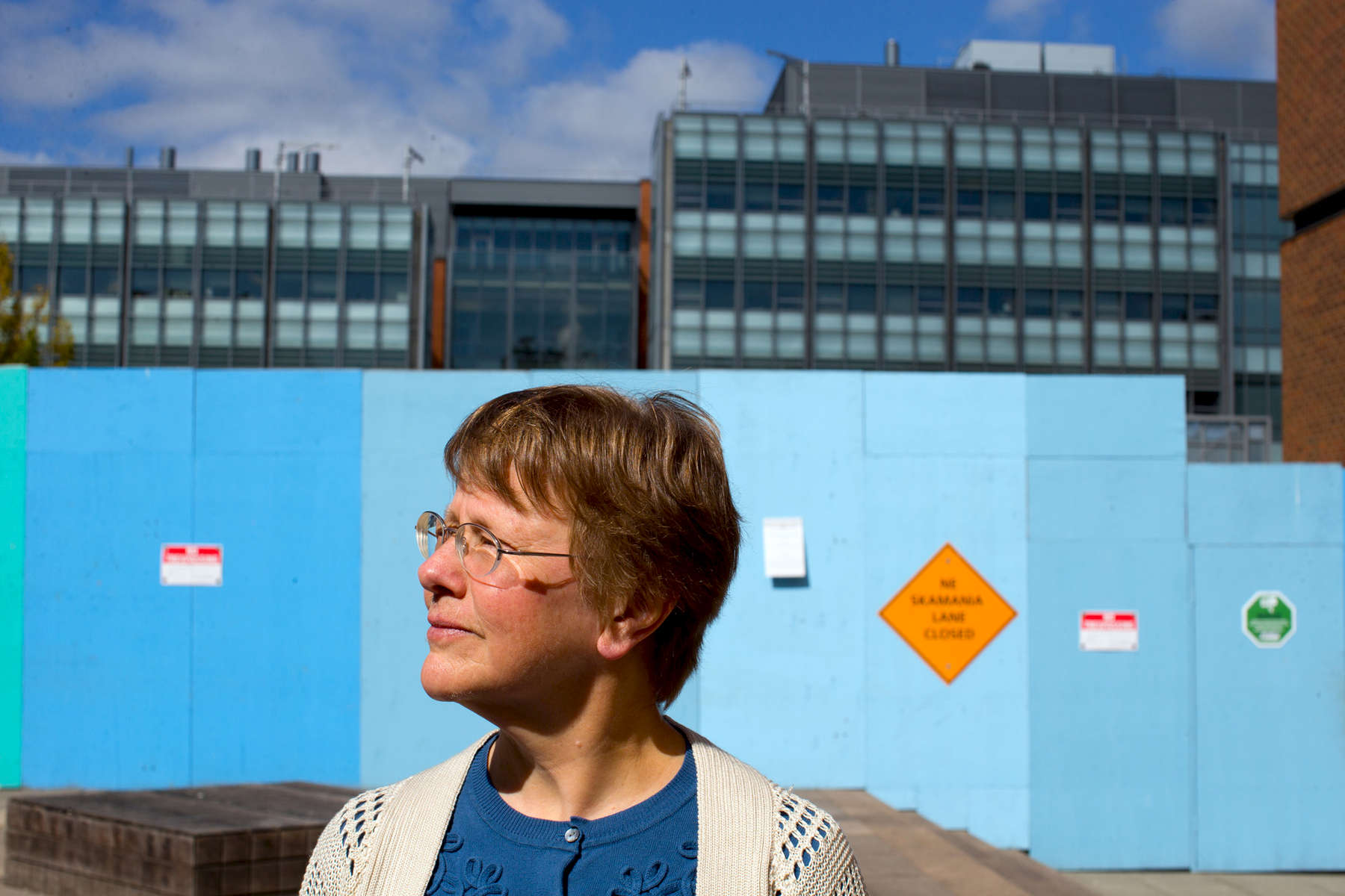 Kathy Bentson, a former research scientist in the Primate Center at the University of Washington, stands in front of a tall, blue wooden wall bearing No Trespassing signs that blocks the public's view of the construction of the new underground animal research lab in Seattle, Wash. on September 21, 2016. In the rear is the William H. Foege Building for Bioengineering and Genome Sciences. Bentson is trying to submit the results of a study she did with others on how to reduce the prevalence of abnormal behaviors in laboratory monkeys to peer review journals, but has met a lot of resistance from the university. (© Karen Ducey Photography)