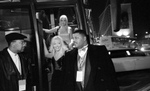 Police officer detective corporal Michael Jackson (right) stands guard as Miss California, Jennifer Jean, exits the beauties' bus outside the Genesis Convention Center on the final night of the Miss USA beauty pageant. © Karen Ducey 2001