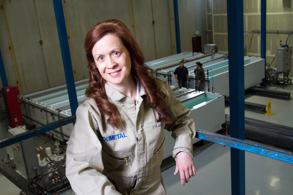 Christina A. Lomasney, CEO of MODUMETAL, Inc, poses in front of the processing line.