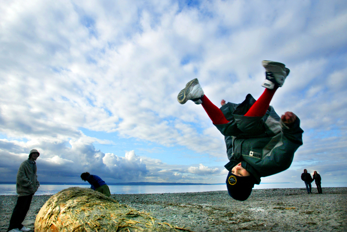 Connelly Brooks does a flip off a log at Carkeek Park in Seattle while his brother, Winfield (left), watches.   Winfield said they decided to spend the day at the park {quote}to enjoy the blue sky{quote}.
