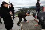 Heidi Lee (left) watches her husband Kenny Lee scribble a name in concrete mix during a ceremony celebrating the freshly poured 43rd story of the eco-luxury Bellevue Towers on May 14, 2008.  The Lee's bought a unit on the 12th floor.  A bucket of concrete mix (in photo) was brought in by a crane for a ceremonial {quote}final Pour{quote}.  Construction is scheduled to be completed in Novemeber 2008 making it the tallest peak in Bellevue. Thanks in part to the elevated grade of the building site, Bellevue Towers is now the cityís tallest peak.