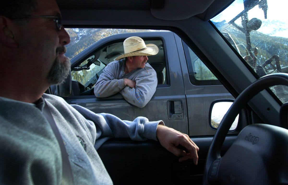 Evan Fink, lead tech from the Washington state Department of Transportation, from Twisp, WA, leans out of his car window to watch a plow shovel snow as he talks with Jeff Adamson (left), DOT communications manager for NW region
