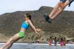 Mackenzie Forman,9 (left) and her brother Chance Forman,8, (feet only) jump into the Franklin D. Roosevelt Lake at Spring Canyon.