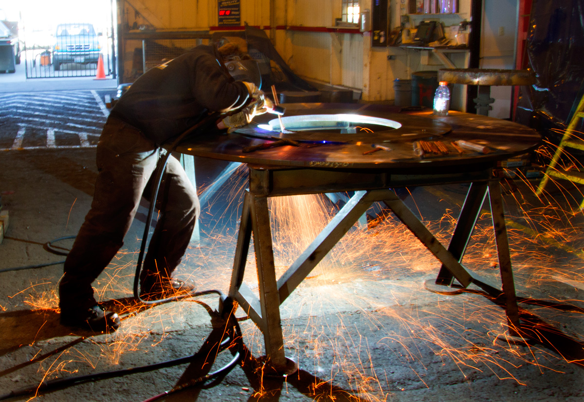 Victor Beal, welder and fitter with Markey Machinery, works on a steel drum meant for a work boat.  Beal has been a welder for six years following in the footsteps of his father. Under the new law in Seattle Beal will receive sick leave in addition to his PTO.