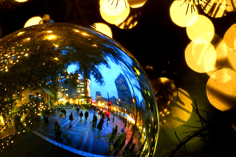 Shoppers in downtown Seattle are reflected in an ornament on the city's official Christmas tree during the holiday season. (© Karen Ducey/Seattle PI)