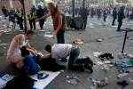 A woman lies hurt after police threw flash bangs into the crowd while rioters burn cars on the downtown streets of Vancouver,BC after the Canucks were defeated by the Boston Bruins in the Stanly Cup on June 15, 2011. (photo copyright Karen Ducey)