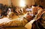 Soldiers with the 3rd Battalion, 1st Brigade of the 101st Airborne Assault Division read men's adult magazines at their makeshift barracks in Al-Kufah during the initial ground assault of the war.