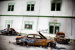 Several torched cars lie in front of the burnt out remains of the Katiba, a Libyan government military complex in Bengazi, where the Libyan revolution began.