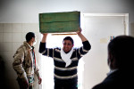 Grieving, a casket bearing relative enters the Jala Hospital morgue in tears to collect the body of a civilian killed by Pro-Gaddafi forces.