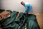A morgue attendant closes the body bag of a killed rebel solider.