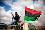 A Libyan rebel smokes amidst the rubble of destroy pro-Gaddafi army vehicles.