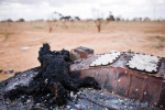 The charred body of a pro-Gaddafi soldier lies sprawled on top of a destroyed loyalist army vehicle along the road to Ajdabiya.