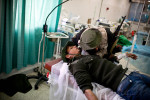 A wounded rebel whispers to his comrade while being treated in the Ras Lanuf hospital.