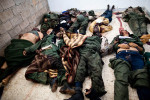 The bodies of Pro-Gaddafi Libyan Army soldiers, killed during battle, are stored in the Jala Hospital morgue. Many are wearing civilian clothes under their army uniforms, raising speculation that they hoped to blend into the civilian populace following the battle.