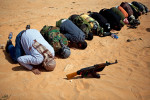 Libyan rebels pray in the desert sand near the front line in Bin Jawad.
