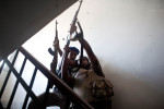 Two Libyan rebels run up a cramped stairway to fire their weapon at a Gaddafi loyalist sniper positioned above them.