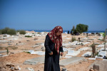 Family members gather at a seaside graveyard to pay their respects for recently deceased loved ones on the morning of the Muslim Eid holiday.