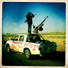 A rebel on the front lines of Ajdabiya looks for pro-Gaddafi force movement during a lull in the battle.