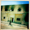 A young Libyan boy rides his bike past a burnt out  government building, following the rebel conquest over the city of Ajdabiya.