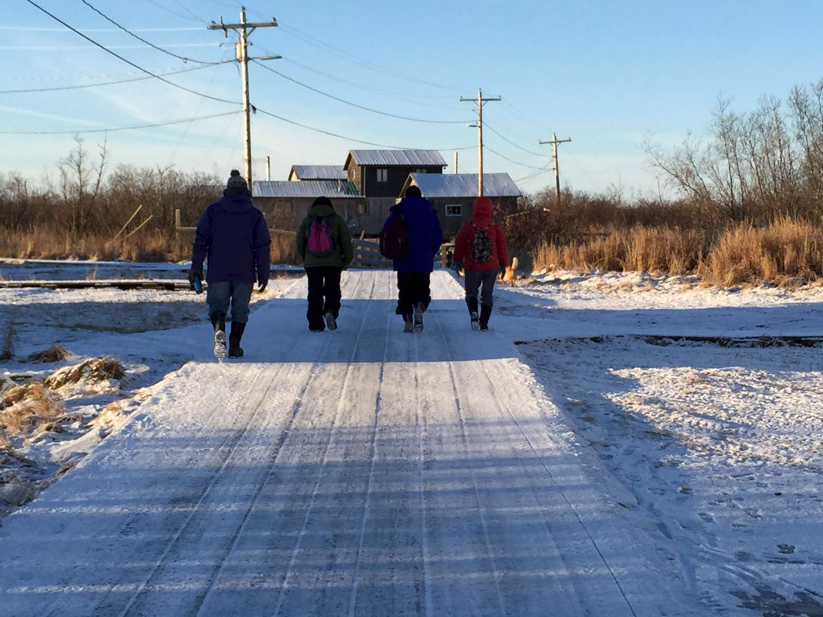 The Calricaraq team walks across the village's wooden sidewalks.