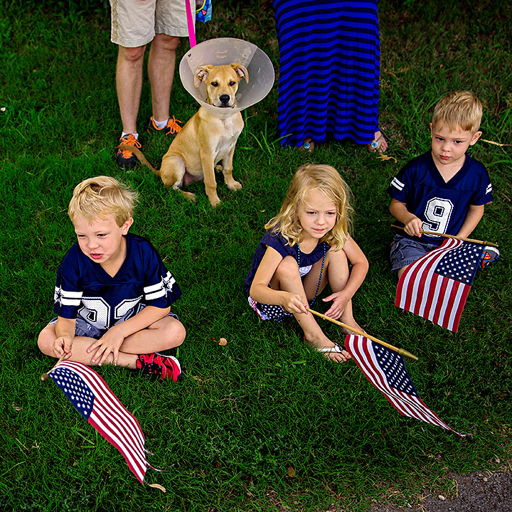 (From left) Ray Hoffman, and siblings Luke Silvers, Marylee Silvers and Jack Silvers watch a parade go by during the Little Forest Hills 4th of July Celebration Friday, July 4, 2014 in Dallas. In its 12th year, the event drew scores of people from the east Dallas neighborhood and featured a parade, music and food. (G.J. McCarthy/The Dallas Morning News)