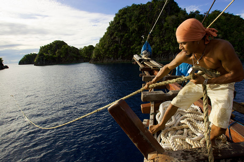 Crewman on the Shakti pulls on a mooring line near smaller island of Fiabacet.
