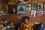 Danuru Sherpa on his iPhone  with photos of his wife and daughters behind him as well as a summit photo from Everest.   His mother Daki Sherpa (age 79) looks in from the kitchen, She has had 8 sons work on the mountain.  5 are still alive