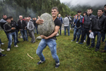 Young men attempt to lift a 300 lb stone (with the goal being to throw it over your head) at the monastery of St. Kvirike and St. Ivlita (Lagurka Church), at the Quiricoba Festival, Kala