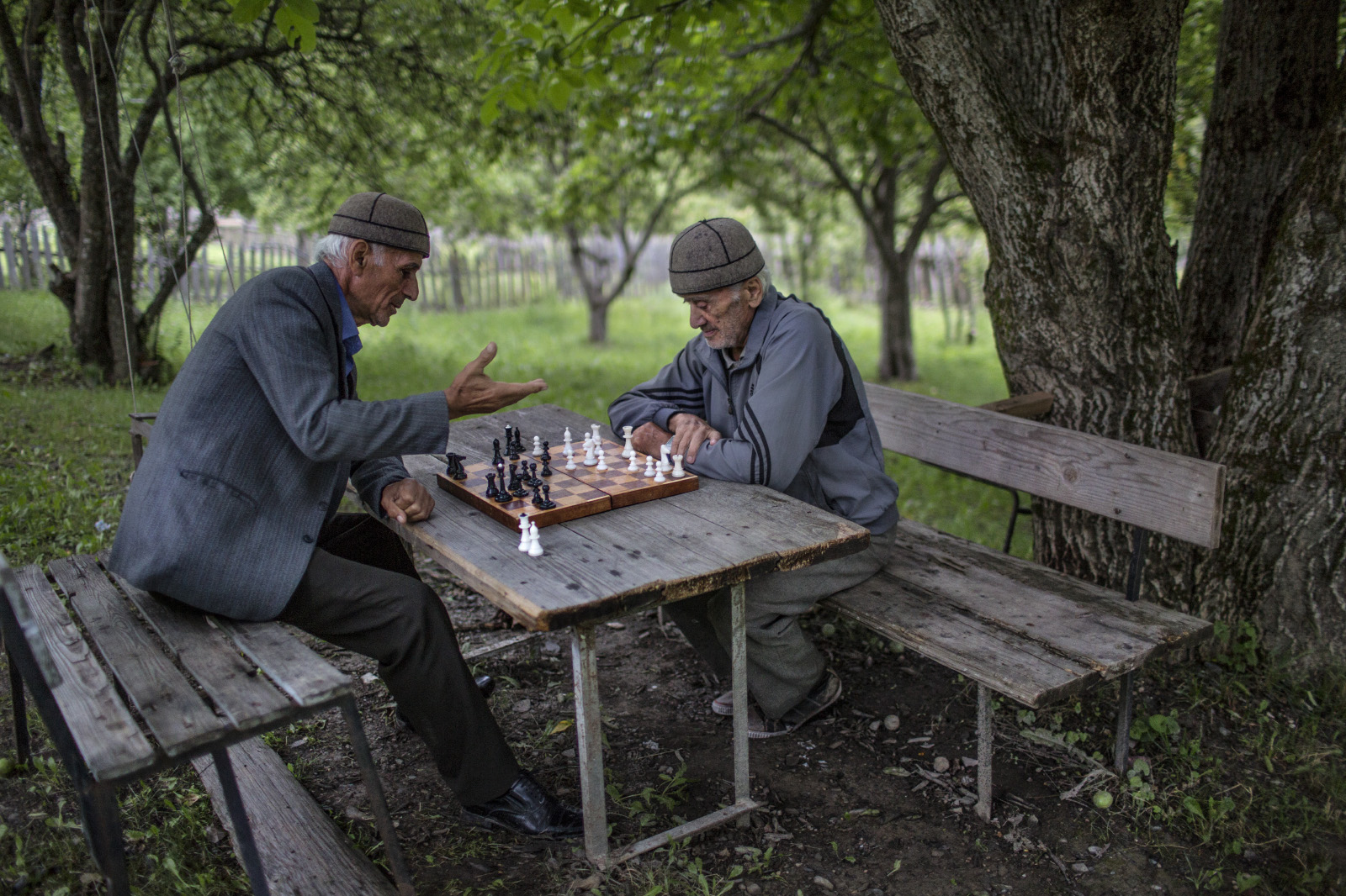 Garantee Pilpani plays chess with family and friends in his back yard, Lengeri