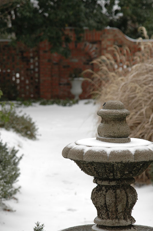 An alternate view of the fountain from the rear courtyard that shows the arched niche off in the wintery distance. This niche is a focal point aloing the backyard crushed path and seperates the home from the neighboring property.