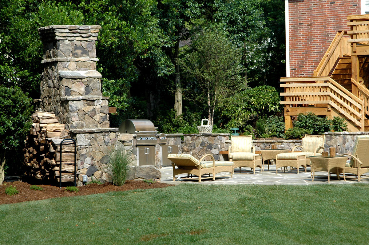 The fireplace wings morph into boulder and stacked stone walls encasing a state-of-the-art grill and stovetop that virtually eliminate multiple trips to the upstairs kitchen. Along with several large boulders and nestled between low stone columns and a raised planter, a 2x8 solid cedar bench supplies additional seating and earthiness to the scene. Similarly, a small semi-circular patio penetrating the main patio consists of oversized field stones with spills of mazus in the joints between.