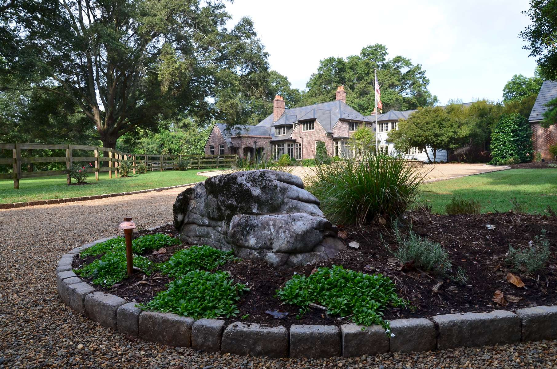 The stone planting bed serves as the first focal point upon entry and delights the senses featuring Mazus, a flowering ground cover, as well as other carefully selected perennials.