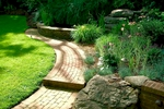 Meandering custom graduated brick walkways lead into an sanctuary filled with fragrance and aesthetics. Hardscapes harmonize alongside softscapes and there is even a custom water feature and outdoor lighting to enhance the senses.