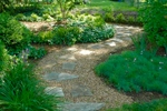 A meandering crushed stone path leads through the entrance garden to the backyard.
