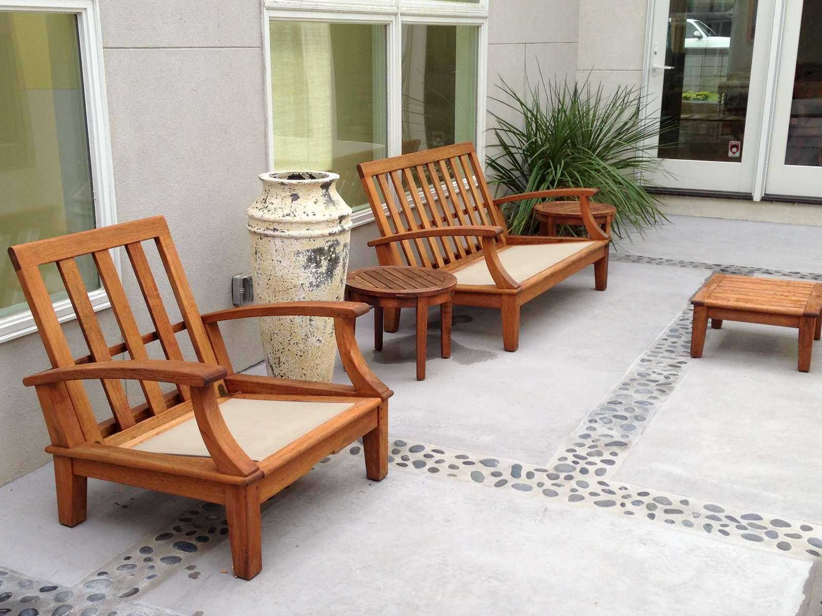 Tucked away to lthe left of the house is an existing private patio. We resurfaced the patio and installed pressed Mexican beach pebbles. Hardwood seating beckons family and friends to relax and linger in the courtyard.