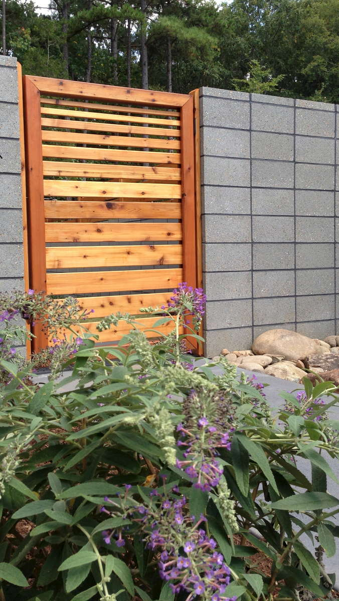A purple butterfly bush in bloom adds a whimsical point of interest against the contemporary feel of the wall and fencing.