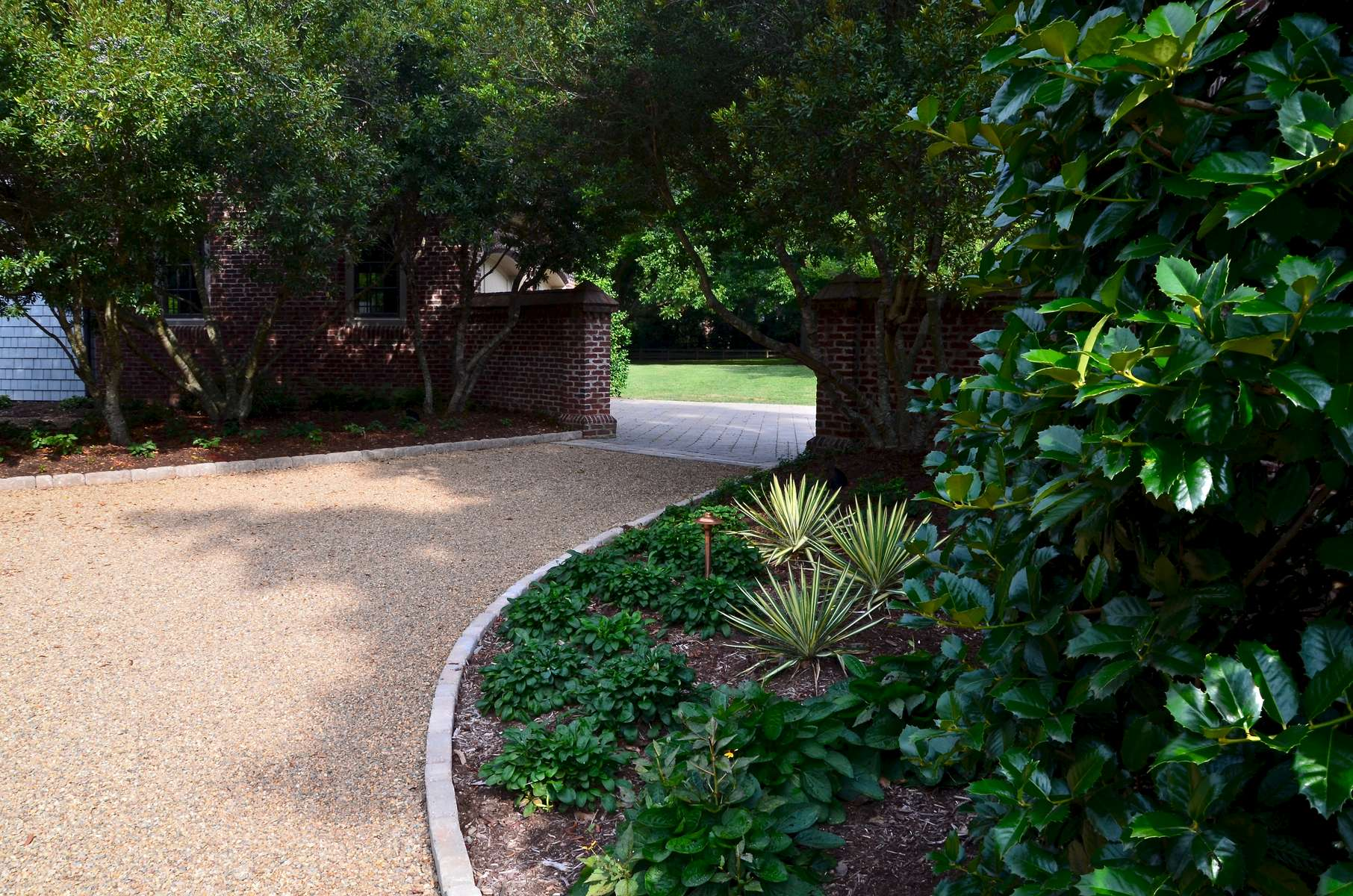 The secondary entrance is flanked by a classic brick columned wall that expands the perimeter. Using the existing wax myrtles trees we also encompassed new complimentary plants such as Yuccas and Ajuga to add depth and dimension. The addition of outdoor lighting also brings ambiance to the space.