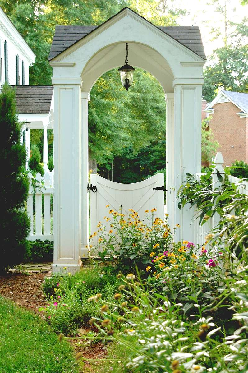 Of timeless design, the white picket fence appears in various interpretations throughout the back yard. Tucked between brick columns, its open picketing gently delineates the property line and includes an arbored gate, inviting neighborly visits. Elsewhere, atop a stone wall and with a scalloped upper pattern, the fence fashionably ensconces a lush lawn beneath the stately grand old oak.