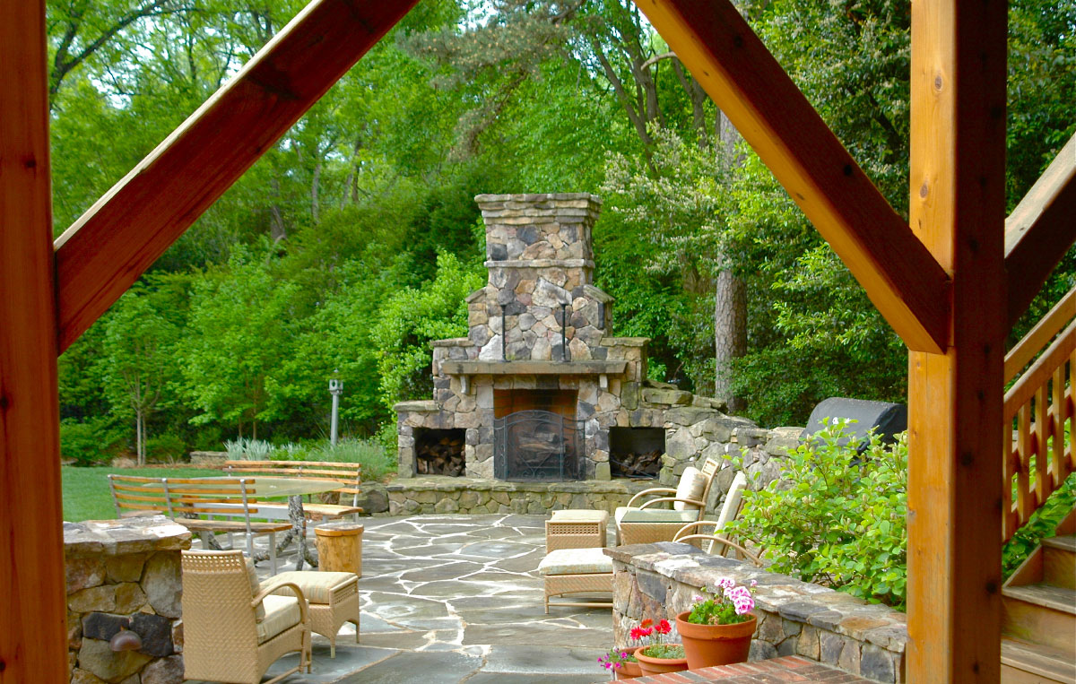 You can also turn right and step down towards the grand focal point on the Tennesee fieldstone patio -- a 13 foot tall custom fireplace with a rough-sawn cedar mantel.Richly stained cedar forms the stairway and railings that wrap a larger deck onto a transitional brick landing. Turn left and on your way to the parking area you'll walk by a splash of ferns, fatsia and hosta nestled beneath the new deck.