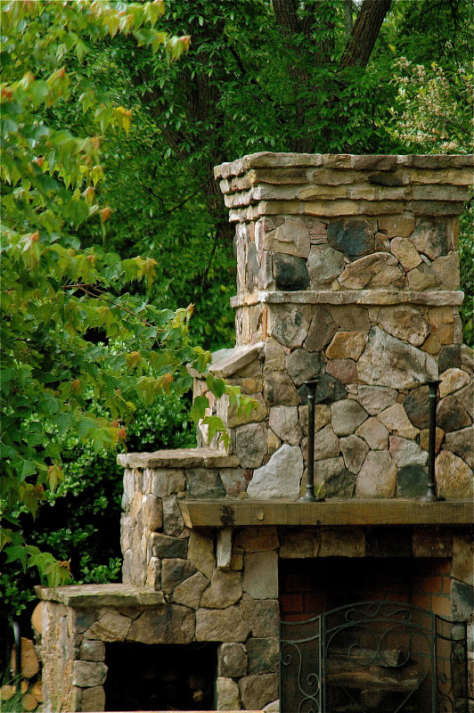 "2"" rockface stone ledges and a heavy stacked stone hearth echo the circular patio. This majestic fireplace undeniably defends the adage ""where there's a hearth, there's a home""!"