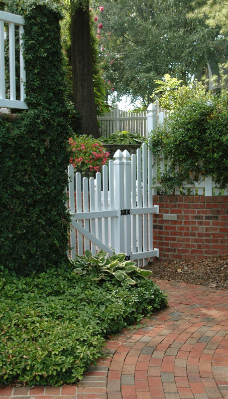 On the opposite side of this garden enclosure is a meaning brick sidewalk passing through a lush, terraced garden that traverses the steep grade from the front to back yard.