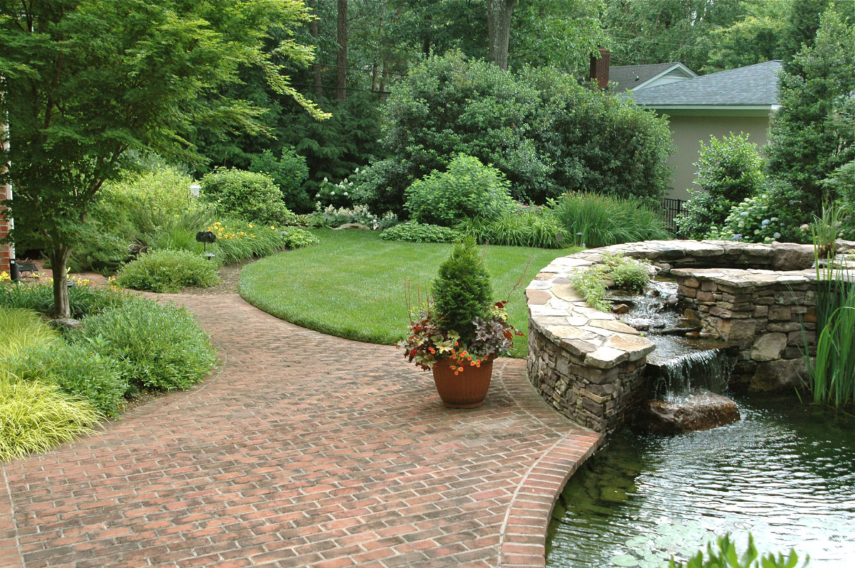 The bricked area adjacent to the water pond serves a dual purpose, as the seperation and connector to the driveway and garage as well as the lead into this lavish backyard.