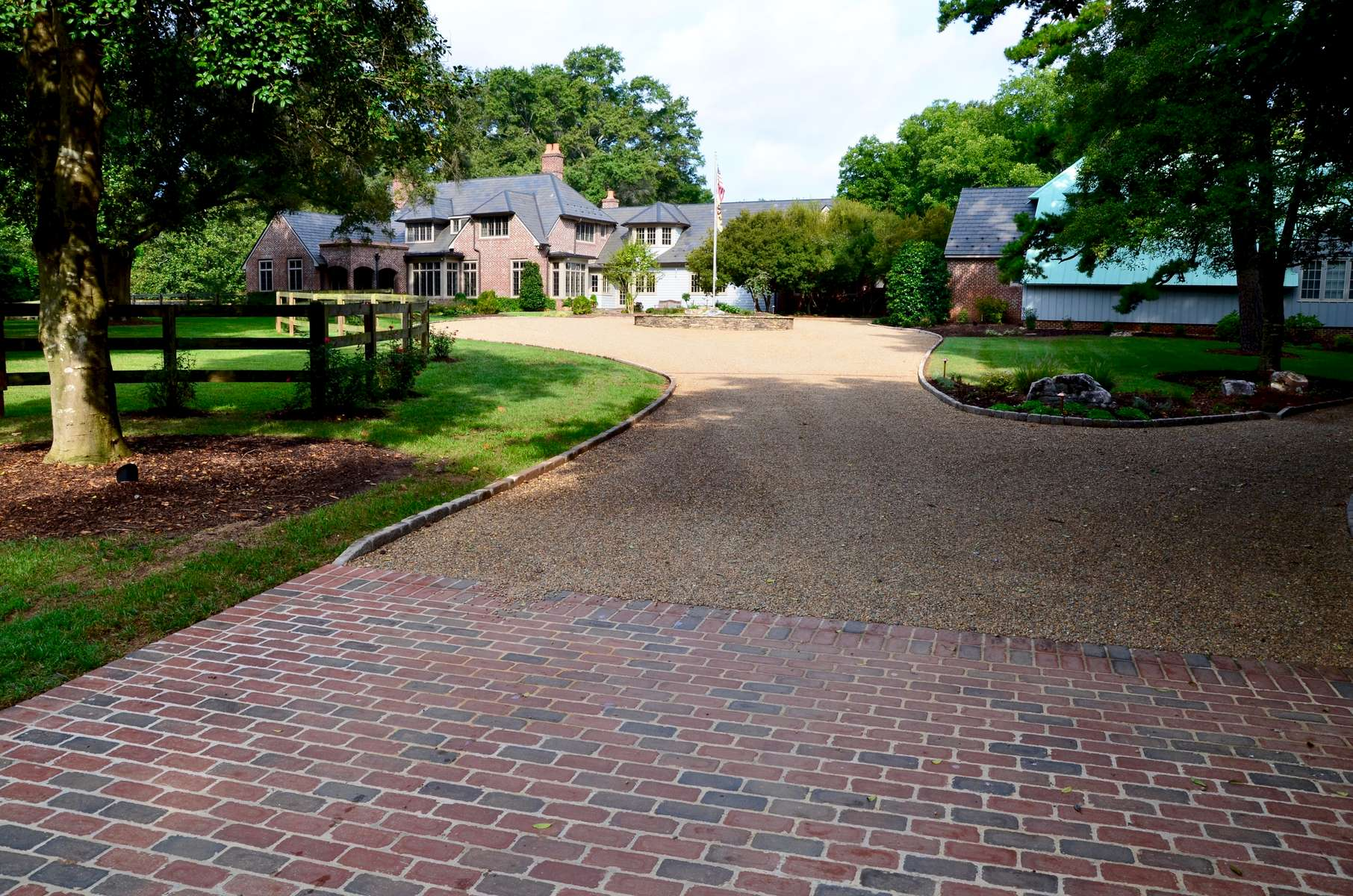Through a complete upgrade of the property's driveway including the area that begins with the brick pad at the street, we installed a cobblestone border that shapes and defines. In addition, Virginia river rock extends throughout the roads within the property.