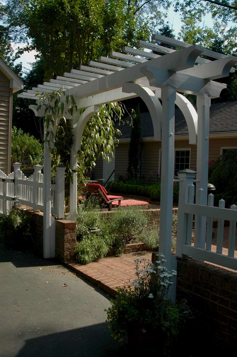 A custom pergola and picket fence seperates the driveway from an intermediate courtyard leading to the back garden.
