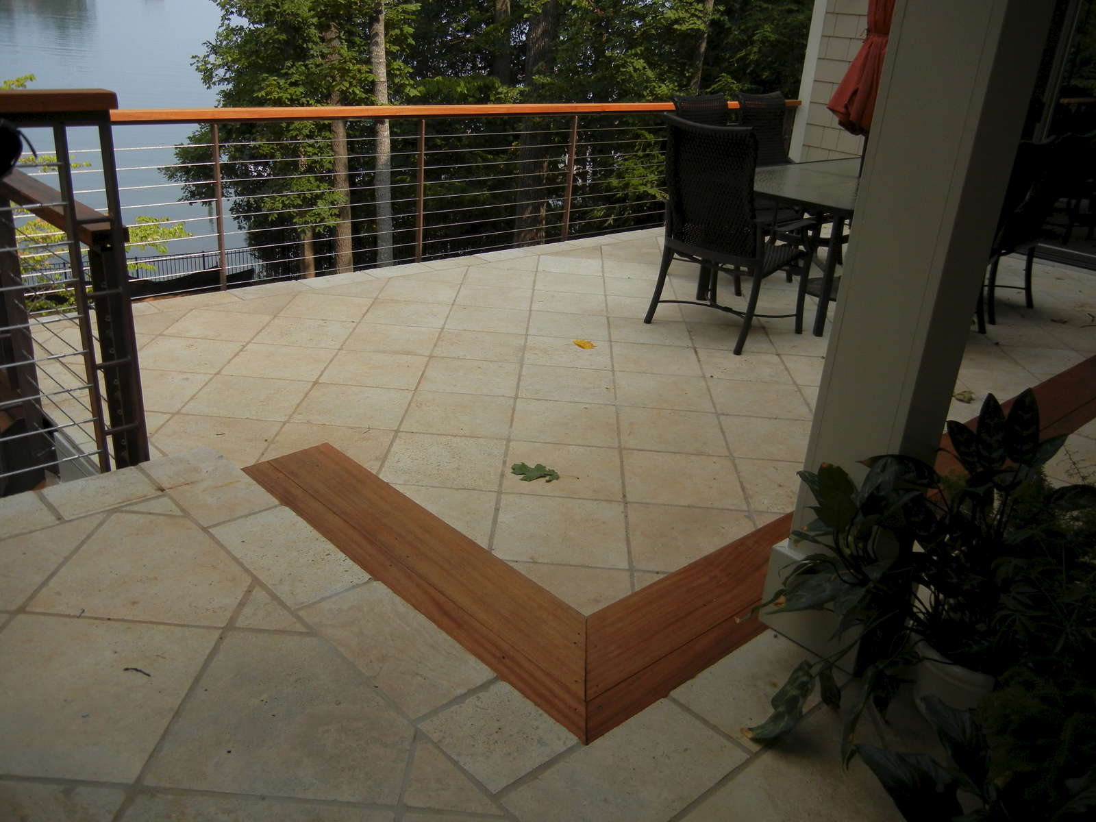 The project includes an urban outdoor living space that includes a sunken Travertine patio with cable rail. The railing helps open up the view and is asethetically appealing.
