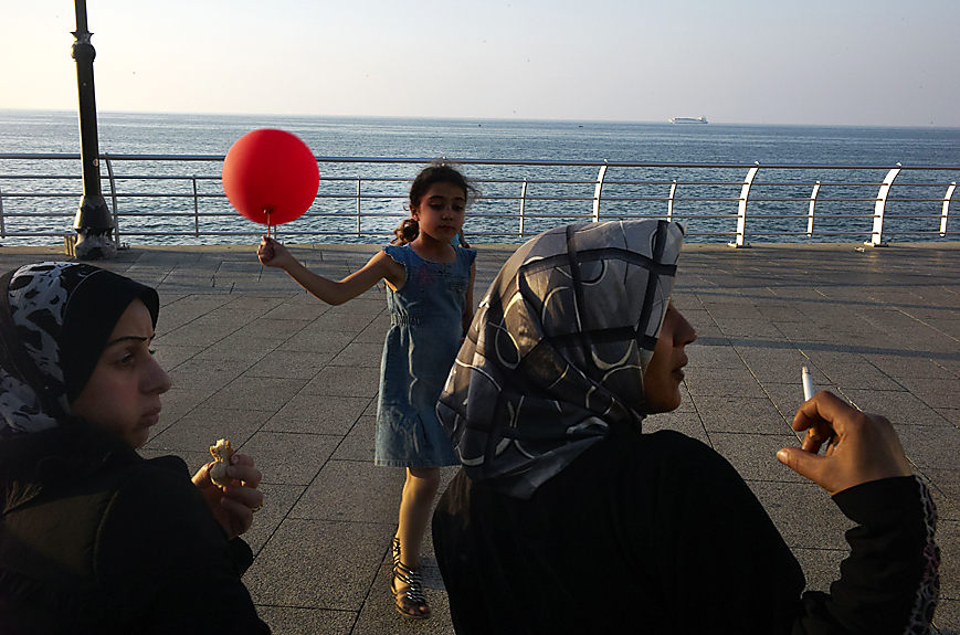 La Corniche, Woman smoking a cigarette while yoiung girl plays with a red ballon, Beirut, May, 2013