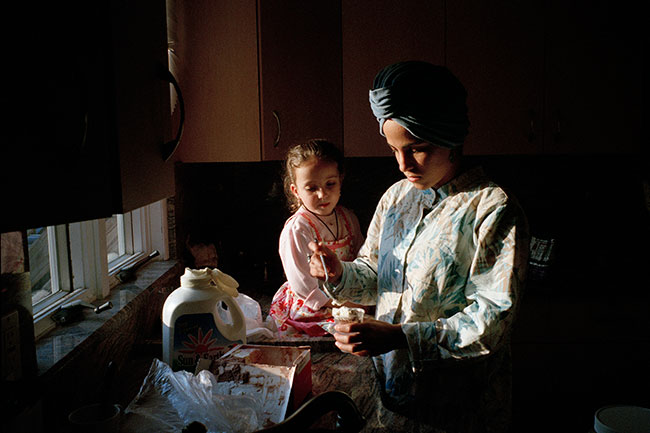 Gitty prepares ice cream for her daughter Esther Miriam in the kitchen of her mother in Kiryas Joel.