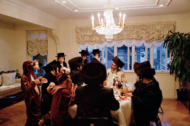 A Satmar family celebrates Purim in Williamsburg. Young men from the Satmar community ask for Charity to the head of each household they visit. Purim is the only night of the year when Hasidic men are allowed to get drunk.
